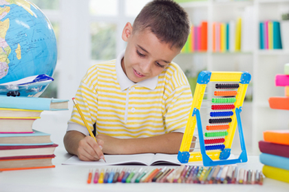 young boy sitting at his desk at home and learn